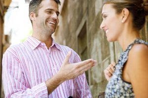 Businessman and businesswoman having an animated conversation outdoors, in a classic city.